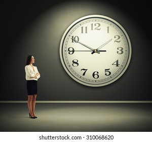 smiley businesswoman standing in dark room with big clock on the wall