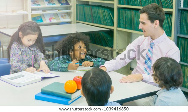 smiley caucasian teacher and grouping of asian kids student learning and talking at white table and color book with bookshelf background