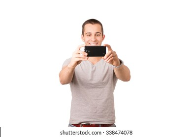 Smiley Caucasian young man is wearing a grey t-shirt and taking a selfie with a black smartphone.