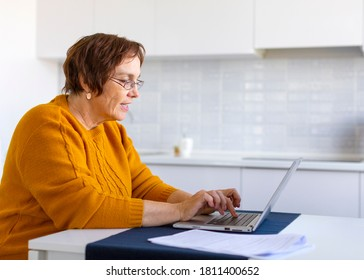 Smiley elder woman working with laptop at home. Distant working concept.