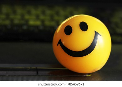 smiley face ball on the black notebook