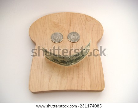 A Smiley Face Formed With Two Silver US Morgan Dollars For The Eyes And A United States Hundred Dollar Note For The Mouth Resting On A Bread Shaped Cutting Board Over White With Slight Vignetting.