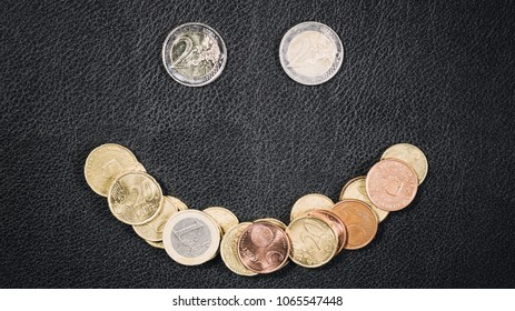 Smiley face made out of many Euro coins over black leather.