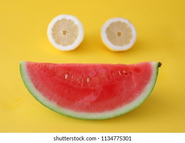 Smiley face made out of a slice of watermelon and two half of a lemon, isolated on bright yellow colored background