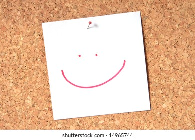 Smiley face pinned to a cork board