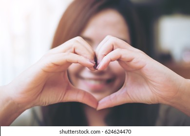 A smiley face woman making heart hand sign over her face with feeling love