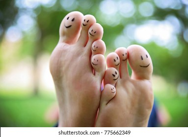 smiley faces on a pair of feet on all ten toes in a park on a hot summer day