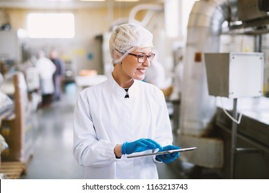 Smiley female worker in sterile clothes using tablet and checking how production line is working.