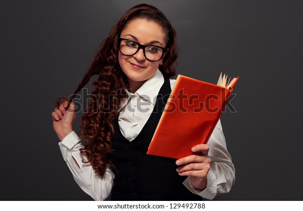 smiley girl in glasses reading a romance over dark background