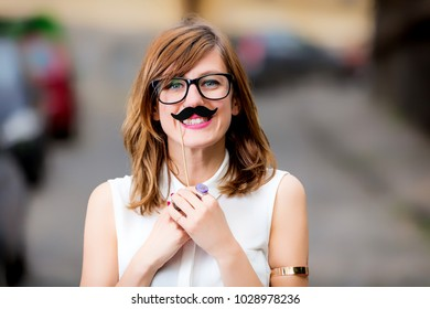Smiley girl pretending to be a man with mustache.
