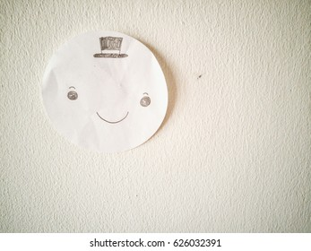 smiley happy face drawing on circle paper sticks on the wall and copy space