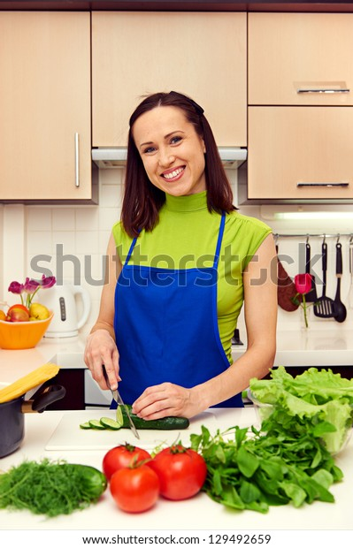 smiley housewife preparing a salad in the kitchen