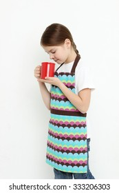 Smiley little girl holding red mug (tea cup)