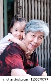 Smiley little girl riding a back of his grandmother. The smiley Asian old lady playing with granddaughter. Concept happy Asia family, Lovely parent, Happiness of the Elderly with family and Cheerful.