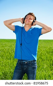smiley man in headphones listening music with pleasure against blue sky and field