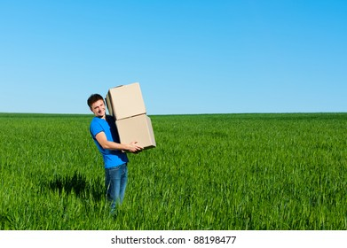 smiley messenger in blue t-shirt carrying boxes