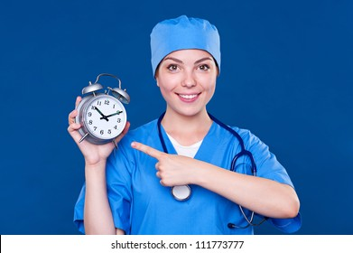smiley nurse pointing at alarm clock. studio shot over blue background