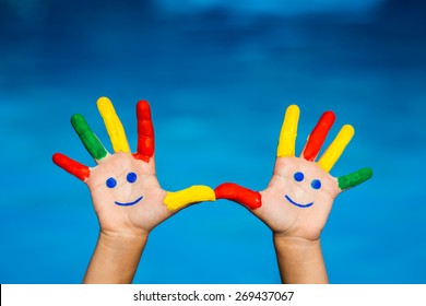 Smiley on hands against blue water background. Summer vacation concept