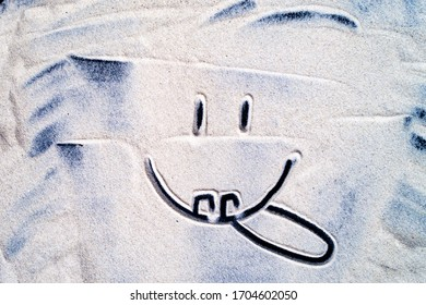 Smiley painted on the sea sand close up