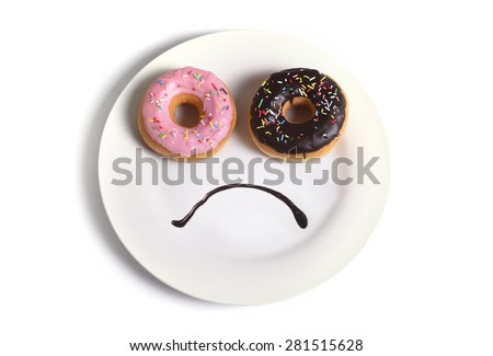 smiley sad face worried about overweight made on dish with donuts as eyes and chocolate syrup as mouth in sugar and sweet addiction , diet and nutrition concept isolated on white background