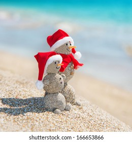 Smiley sandy snowmen couple at sea beach in christmas hat. New years holiday in hot countries concept.