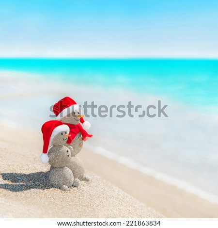 e1379dd8 Smiley sandy snowmen couple at sea beach in christmas hat. New years  holiday in hot