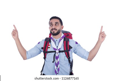 Smiley scout man carrying the rucksack looking up pointing with finger in every hand, isolated on a white background.