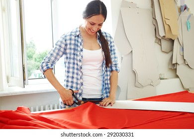 smiley seamstress working with  pattern and red textile