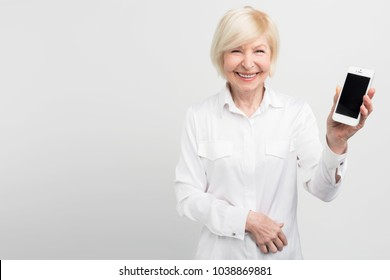Smiley senior woman is holding a new smartphone in her hand. She has learned how to use it. She is passioned about internet and new technologies. Isolated on white background.
