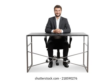 smiley successful businessman sitting at the table and looking at camera. isolated on white background