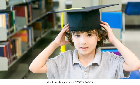 smiley white boy with the Graduation cap and diploma paper stands and smile in the shelf of books background.