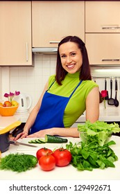 smiley woman in apron standing in the kitchen