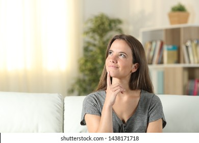 Smiley woman thinking looking at side sitting on a couch at home