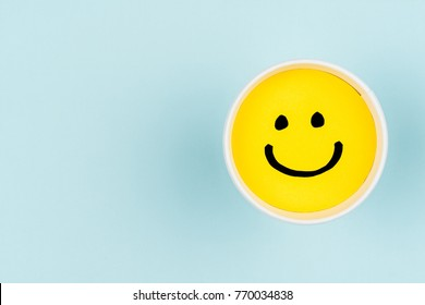 Smiley yellow face on blue background with copy space