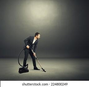 smiley young businessman in formal wear vacuuming dark room