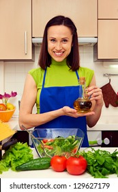 smiley young housewife holding olive oil and looking at camera