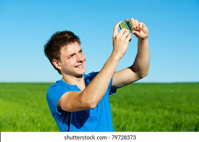 smiley young man taking picture on phone