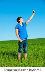 smiley young man taking picture on phone against green grass and blue sky