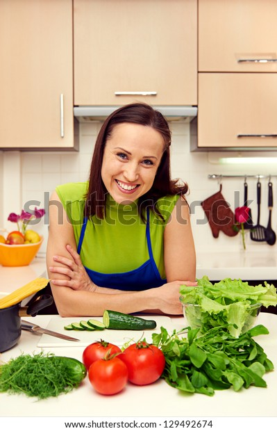 smiley young woman with vegetables in kitchen