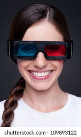 smiley young woman watching 3d film in stereo glasses