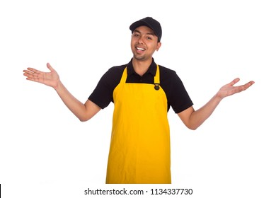 Smiley young worker wear cap and yellow apron raising hands saying surprise after finishing the work isolated on a white background.