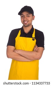 Smiley young worker wearing cap and yellow apron standing crossed arms isolated on a white background.