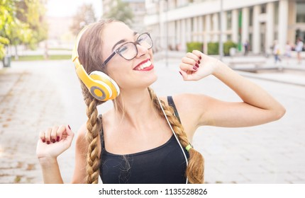 smilin young woma listen music with headphone and dance