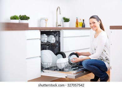Smiling 20s woman in kitchen, empty out the full dishwasher