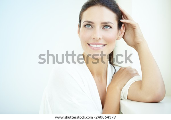 Smiling 30 year old woman at the window. Fresh light blue background.