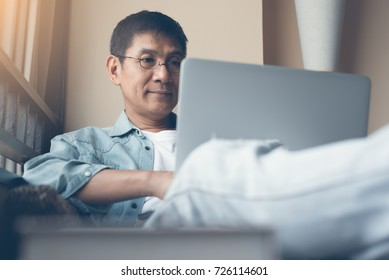 Smiling 40s asian man with glasses working on laptop computer leaning on armchair at home. Casual businessman or freelancer relaxed working from home, internet of things IoT concept, vintage tone