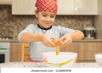 Smiling 7 year old boy helping in the kitchen, breaking eggs into large bowl.