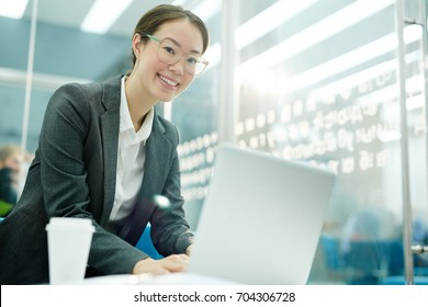 Smiling accountant looking at camera while typing or networking in office