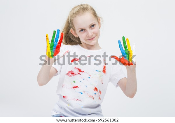 Smiling Active Caucasian Young Girl With Messy Colorful Palms While Making Handprints On T-Shirt With Fresh Paint. Against White Background. Horizontal Image Composition