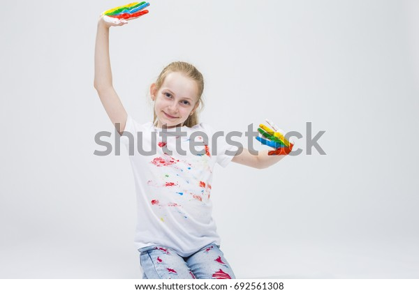 Smiling Active Caucasian Young Girl With Messy Colorful Palms While Making Handprints On T-Shirt With Fresh Paint. Against White Background. Horizontal Image Oientation